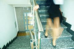 blurred outline of businesswoman with briefcase going down the stairway - stock photo