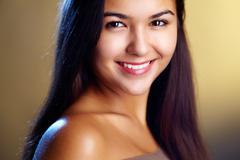 young girl smiling charmingly at camera - stock photo