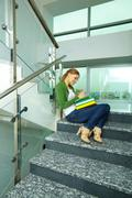 Portrait of pretty girl sitting on stairs and making notes in copybook Stock Photos