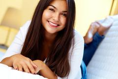 Portrait of pretty carefree teenager looking at camera and smiling Stock Photos