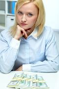 portrait of serious woman with banknotes lying in front of her on table - stock photo