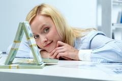 portrait of a young smiling woman and house of banknotes - stock photo