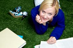 Stock Photo of high angle view of young student lying on grass with textbooks
