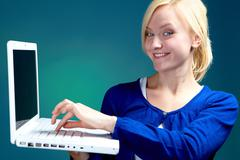 young smiling woman pressing button on a laptop - stock photo