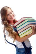 Stock Photo of cute girl with several books smiling at camera in isolation