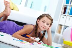 Stock Photo of portrait of lovely girl drawing with colorful pencils