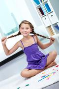 Stock Photo of portrait of young smiling child with pigtails posing in front of camera