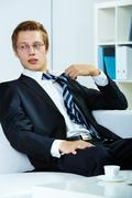 Portrait of a successful employer at workplace untying necktie Stock Photos