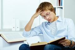 Image of serious student reading book Stock Photos