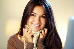 image of young woman with dark long hair smiling at camera - stock photo