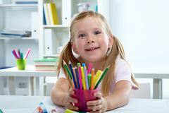 portrait of lovely girl with colorful crayons - stock photo