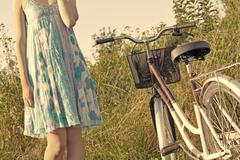A young girl in a blue dress with a vintage bike in the meadow, retro feel Stock Photos