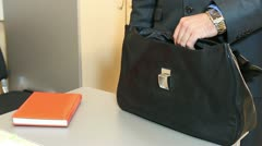 Close-up of leather briefcase in male hand. Man putting notebook into his bag. - stock footage