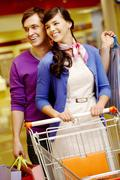 portrait of happy couple shopping in the mall - stock photo