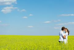 Image of happy couple embracing in yellow meadow at summer Stock Photos