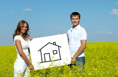 portrait of happy young couple showing house drwan on paper in meadow - stock photo