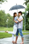 Portrait of woman and man embracing under umbrella during rain Stock Photos