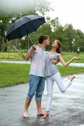 Portrait of woman and man under umbrella during rain Stock Photos