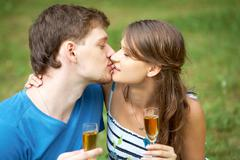 portrait of man and his girlfriend holding flutes with alcohol and kissing - stock photo