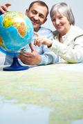 portrait of happy senior couple looking at globe - stock photo