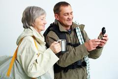 portrait of happy senior couple looking at compass on trip - stock photo