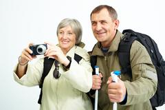 Portrait of happy senior couple going to take photo of something during trip Stock Photos