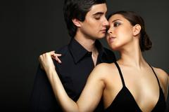 Portrait of elegant girl with handsome man near by on black background Stock Photos