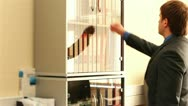 Stock Video Footage of Shelf with folders for documents. Business man near the shelves with folders.