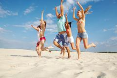 Photo of happy friends running down sandy beach with raised arms Stock Photos
