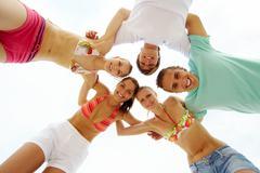 below view of joyful teens looking at camera with smiles - stock photo