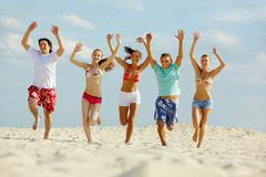 photo of happy friends running down sandy beach on background of cloudy sky - stock photo