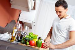 Portrait of young man cutting vegetables in the kitchen Stock Photos
