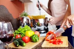 close-up of young man cutting vegetables in the kitchen - stock photo