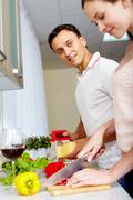Portrait of amorous couple cooking salad in the kitchen Stock Photos