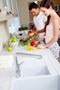 Stock Photo of portrait of amorous couple cooking salad in the kitchen