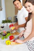 portrait of amorous couple cooking salad in the kitchen - stock photo