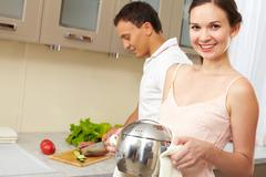 portrait of happy female with pan looking at camera while her husband cooking sa - stock photo