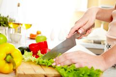 Close-up of young female cutting lettuce in the kitchen Stock Photos
