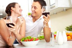 image of happy couple with glasses of red wine eating salad - stock photo