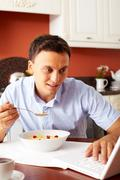 Portrait of handsome man eating snacks with milk in the kitchen while typing Stock Photos