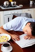 Portrait of man sleeping on laptop keypad with bowl of snacks and cup of coffee Stock Photos