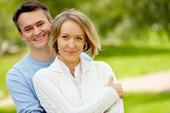 portrait of young happy couple looking at camera outdoors - stock photo