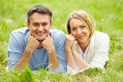 Portrait of young couple looking at camera while lying on green grass Stock Photos