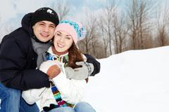 Portrait of happy couple in warm clothes embracing and looking at camera Stock Photos