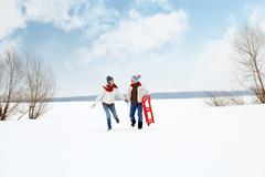 portrait of happy couple in warm clothes running outdoors in winter - stock photo