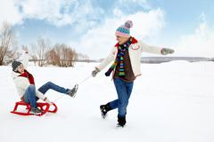 Portrait of happy couple in warm clothes tobogganing in winter Stock Photos