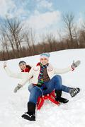 portrait of happy couple in warm clothes tobogganing in winter - stock photo