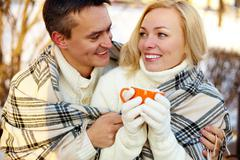 photo of happy man and pretty woman with cups outdoor in winter - stock photo