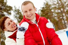 portrait of happy couple in warm clothes spending winter vacation - stock photo