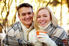 photo of happy man and woman with cups looking at camera outdoors in winter - stock photo